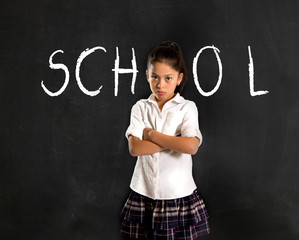 hispanic moody little schoolgirl in uniform standing upset