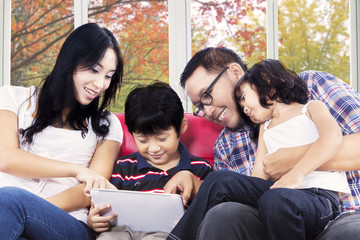 Hispanic family playing digital tablet