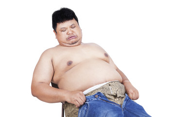 Obese man trying to wear his old jeans