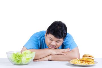 Obese man looking at salad