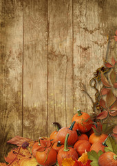Autumn leaves and pumpkins on a wooden background