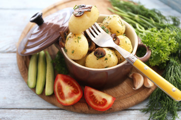 Young boiled potatoes in pan with vegetables