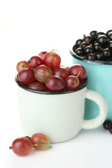 Ripe gooseberries and blackcurrants in mug isolated on white.