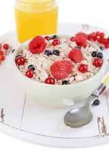 Tasty oatmeal with berries in bowl close-up