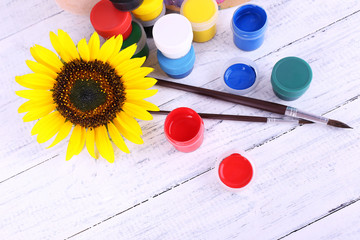 Paints, brushes and sunflower on wooden background