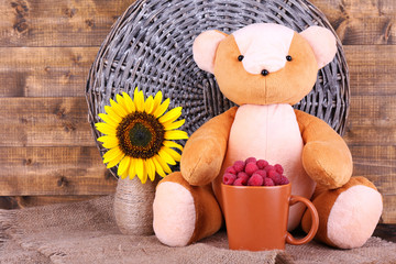 Toy bear and mug of raspberries and flowers