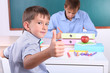 Schoolboy and teacher sitting in classroom
