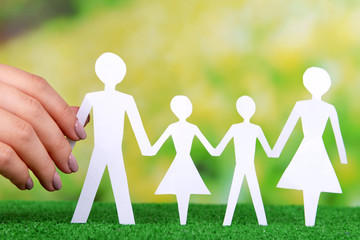 Woman hand holding paper family on grass on bright background
