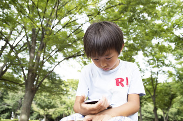 Boy with a mobile phone in the park