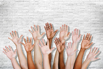 Group of Human Arms Raised with Brick Wall