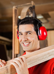 Happy Carpenter Carrying Wooden Plank On Shoulder