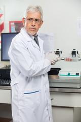 Scientist Standing By Analyzer In Lab