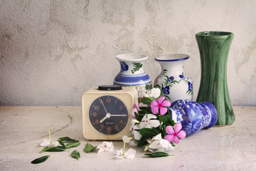 flowers and alarm clocks on wooden table