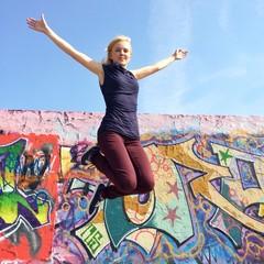 Mädchen macht Luftsprung vor Mauer