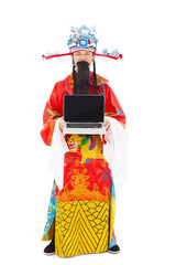 God of wealth standing and  holding a laptop