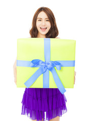 happy young woman holding a gift box over white background