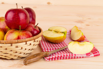 Ripe apples with knife on wooden table.