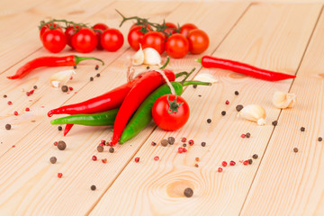 Hot peppers with tomatoes on wood.