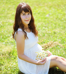 Pretty pregnant woman with flowers on the grass summer