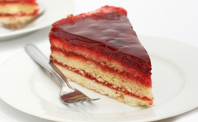 Two pieces of homemade biscuit cake with raspberry jam and jelly