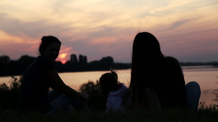 Silhouette of three girls with a child.