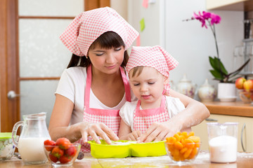 Young woman and her daughter making berry fruit cake