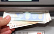 man takes money in EURO banknotes from an ATM