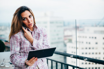 Young businesswoman talking on phone and using tablet computer i