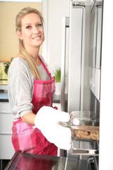 Frau steht am Ofen