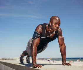 Muscular man doing push ups against blue sky