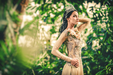 Woman with tiara on a head posing in a forest