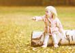 Little cute girl shows gesture hands toward, autumn