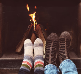 Romantic legs of a couple in socks in front of fireplace at wint