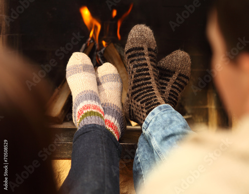 canvas print picture Legs of a couple in socks in front of fireplace at winter season