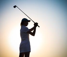 Female golfer at sunset