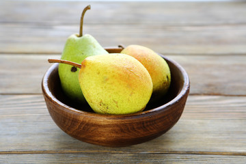 fresh pear in wooden bowl