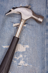 Hammer black handle tool with torn blue jeans pattern background