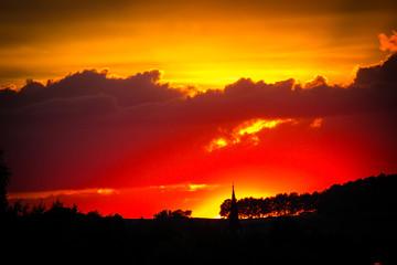 Kirchturm vor rotem Sonnenuntergang im Herbst Jesus ist da