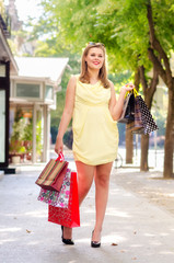 Beautiful urban girl standing on the street after shopping