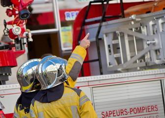 Firefighters discussing next to fire truck, Geneva, Switzerland