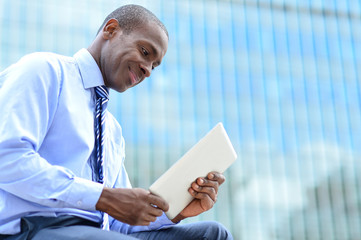 Smiling corporate executive using a tablet pc