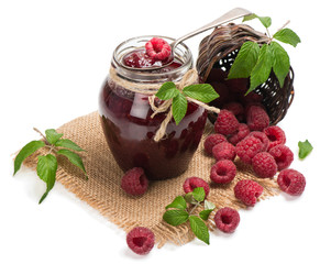 Homemade  raspberry jam in a jar and berries aside