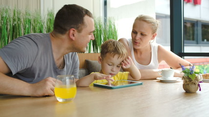 Family of three with pad in cafe