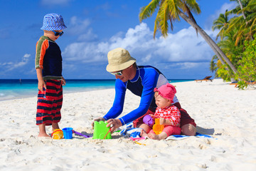 Father and kids making sand castle at beach