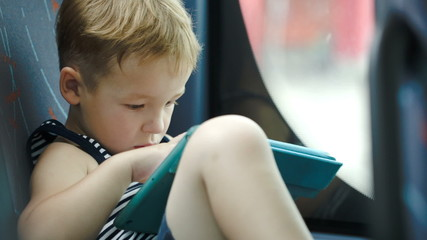 Little boy in car using tablet computer
