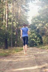 Athletische junge Frau läuft im Wald, Blick von hinten