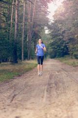 Athletische Frau geht im Wald joggen