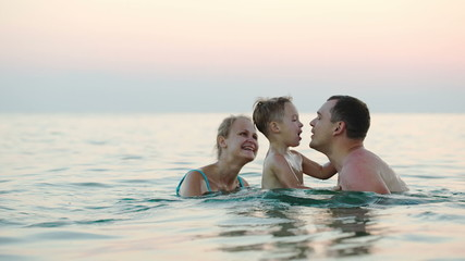 Happy family of three bathing in sea