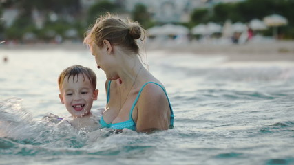 Little boy having fun with mother in sea