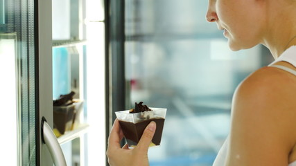 Woman taking cake from fridge at the shop